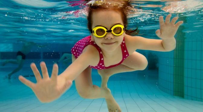 smiling girl swimming underwater