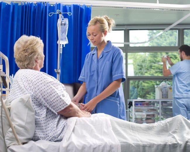 nurse checks patient's IV