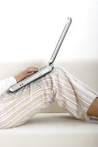 Wearing pyjamas and using laptop