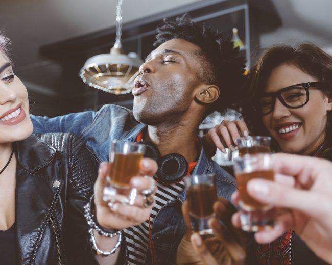 Happy friends drinking shots